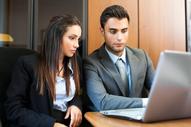Twee jonge partners die plannen of ideeën bespreken op vergadering