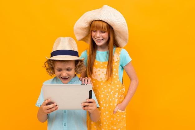 Twee jonge roodharige vrienden met de zomerhoeden kozen vakantiepakketten geïsoleerde gele achtergrond