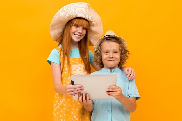 Twee jonge roodharige vrienden met zomerhoeden kozen vakantiepakketten op een gele achtergrond