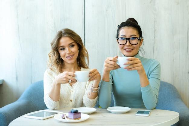 Twee jonge rustgevende interculturele vrouwtjes met kopjes cappuccino zittend op een comfortabele bank bij tafel in café