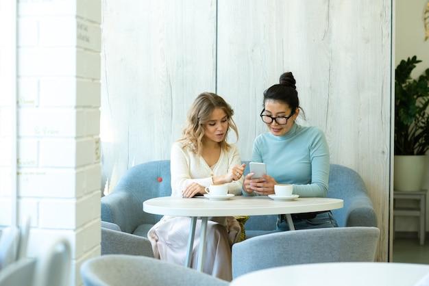 Twee jonge rustgevende vrouwen in vrijetijdskleding bespreken onlineproducten in smartphone zittend aan tafel in comfortabel café