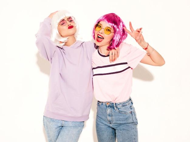 Twee jonge sexy hipster meisjes in pruiken en rode lippen. mooie trendy vrouwen in zomer kleding in zonnebril