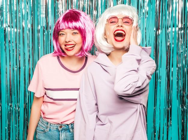 Twee jonge sexy hipster meisjes in pruiken en rode lippen. mooie trendy vrouwen in zomer kleding plezier