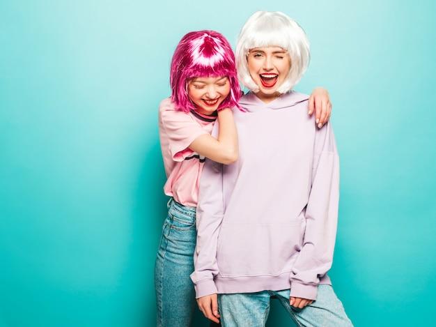 Twee jonge sexy hipster meisjes in pruiken en rode lippen. mooie trendy vrouwen in zomer kleding. zorgeloze modellen poseren in de buurt van blauwe muur in studio gek