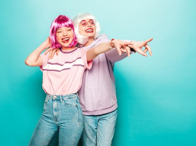 Twee jonge sexy hipster meisjes in pruiken en rode lippen. mooie trendy vrouwen in zomer kleding. zorgeloze modellen poseren in de buurt van blauwe muur in studio wijzen op winkelverkoop