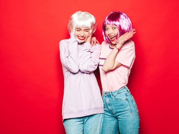 Twee jonge sexy hipster meisjes in pruiken en rode lippen. mooie trendy vrouwen in zomer kleding. zorgeloze modellen poseren in de buurt van rode muur in studio gek
