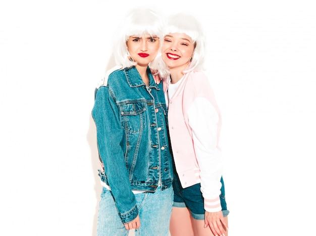 Twee jonge sexy hipster meisjes in witte pruiken en rode lippen in zonnebril
