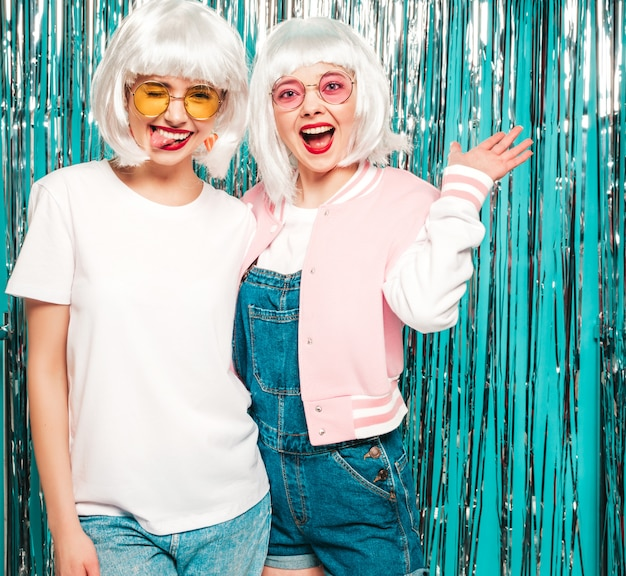 Twee jonge sexy hipster meisjes in witte pruiken en rode lippen. mooie trendy vrouwen in de zomer kleding zomer in zonnebril