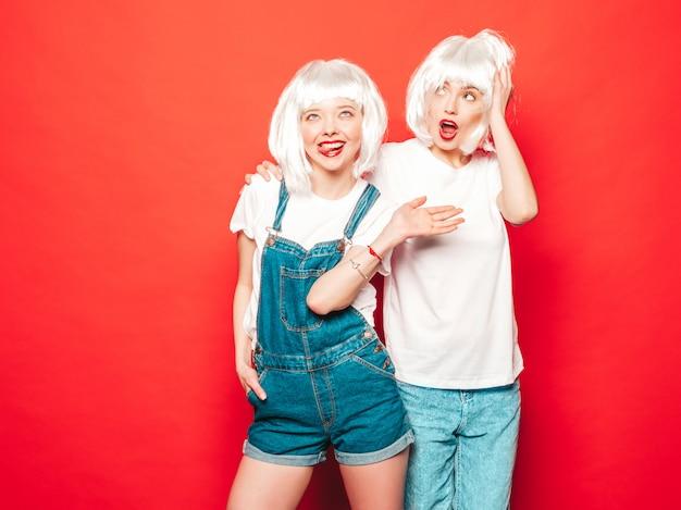 Twee jonge sexy hipster meisjes in witte pruiken en rode lippen. mooie trendy vrouwen in zomer kleding. zorgeloze modellen poseren in de buurt van rode muur in studio zomer in zonnebril