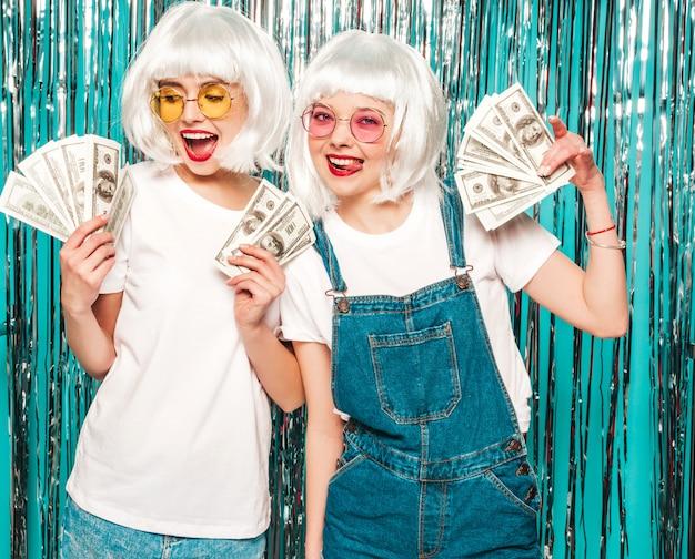 Twee jonge sexy hipster meisjes in witte pruiken en rode lippen. mooie vrouwen met dollars in handen zomer zakgeld