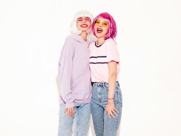 Twee jonge sexy lachende hipster meisjes in pruiken en rode lippen. mooie trendy vrouwen in de zomer kleding. zorgeloze modellen poseren in de buurt van witte muur in studio gek en knuffelen