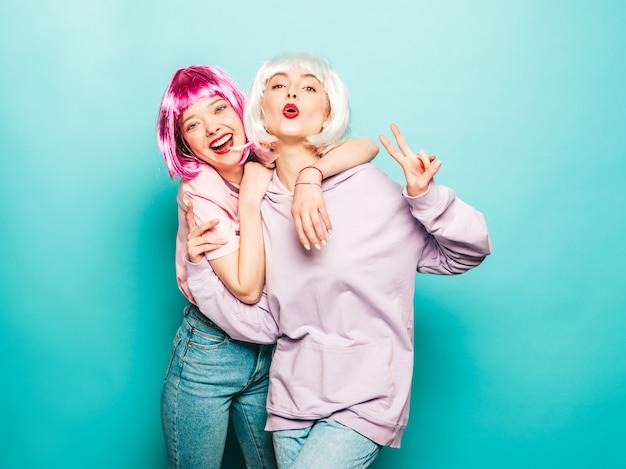 Twee jonge sexy lachende hipster meisjes in pruiken en rode lippen. mooie trendy vrouwen in zomer kleding. zorgeloze modellen poseren in de buurt van blauwe muur in studio toont vredesteken