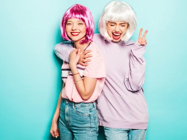 Twee jonge sexy lachende hipster meisjes in pruiken en rode lippen. mooie trendy vrouwen in zomer kleding. zorgeloze modellen poseren in de buurt van blauwe muur in studio vrede teken tonen