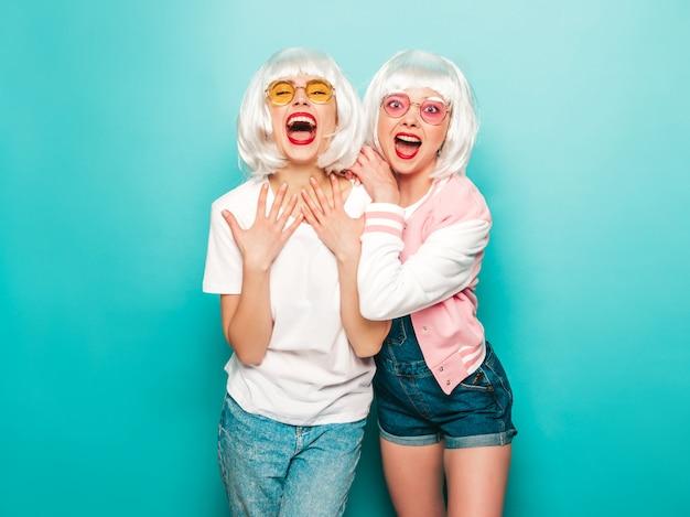 Twee jonge sexy lachende hipster meisjes in pruiken en rode lippen. mooie trendy vrouwen in zomer kleding. zorgeloze modellen poseren in de buurt van blauwe muur in studio zomer geschokt en verrast