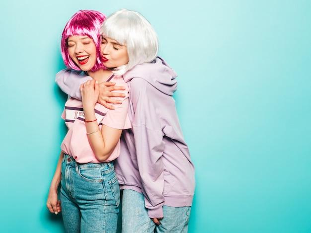 Twee jonge sexy lachende hipster meisjes in pruiken en rode lippen. mooie trendy vrouwen in zomer kleding. zorgeloze modellen poseren in de buurt van blauwe muur in studio