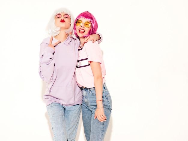 Twee jonge sexy lachende hipster meisjes in pruiken en rode lippen. mooie trendy vrouwen in zomer kleding. zorgeloze modellen poseren in de buurt van witte muur in studio gek en toont vredesteken