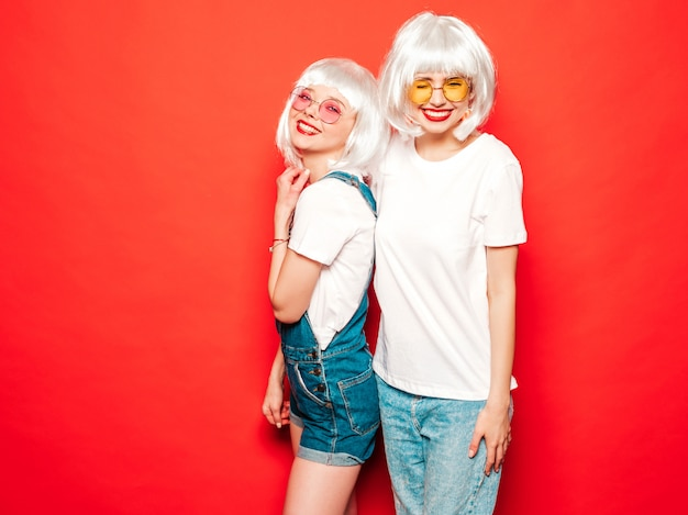 Twee jonge sexy lachende hipster meisjes in witte pruiken en rode lippen. mooie trendy vrouwen in de zomer kleding. zorgeloze modellen poseren in de buurt van rode muur in studio zomer gek
