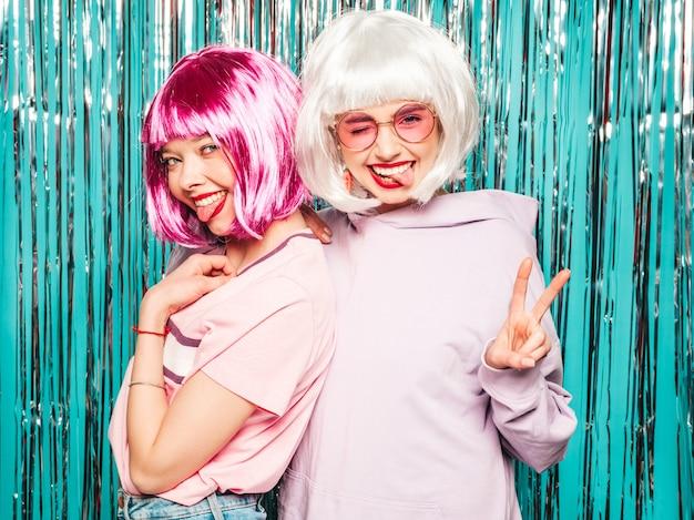 Twee jonge sexy lachende hipster meisjes in witte pruiken en rode lippen. mooie trendy vrouwen in de zomer kleding