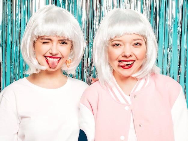 Twee jonge sexy lachende hipster meisjes in witte pruiken en rode lippen. mooie trendy vrouwen in zomer kleding. ze tonen tongen