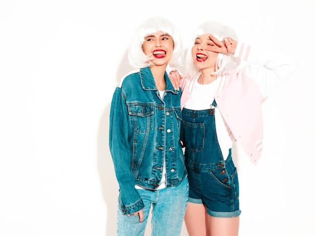 Twee jonge sexy lachende hipster meisjes in witte pruiken en rode lippen zomer toont tong en vredesteken