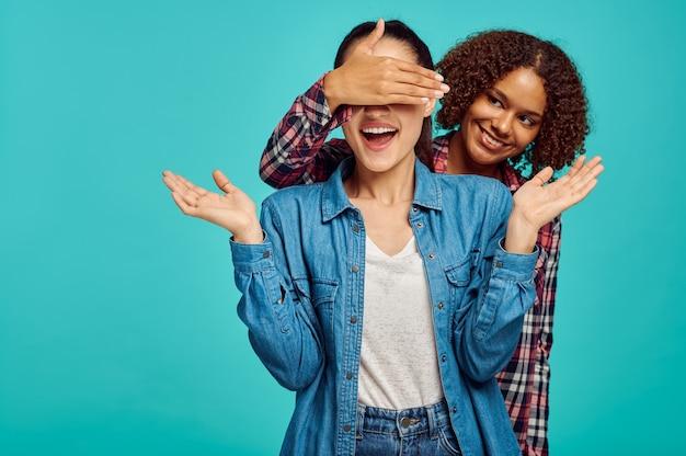 Twee jonge speelse dames, blauwe muur, positieve emotie. gezichtsuitdrukking, vrouwelijke persoon op zoek op camera in studio, emotioneel concept, gevoelens