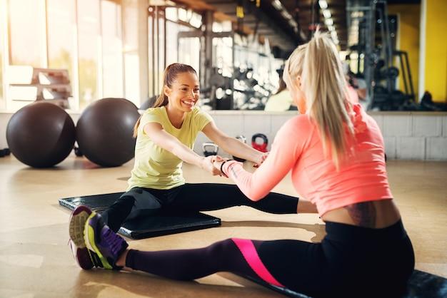Twee jonge sportieve meisjes strekken hun benen na zware training. tegen elkaar zitten met rafelige benen.