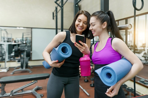 Twee jonge sportvrouwen in gymnastiek het spreken glimlachend met geschiktheidsmatten