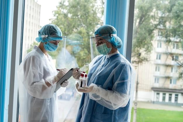 Twee jonge stagiaires werken met reageerbuisjes met bloed voor laboratoriumonderzoek om een nieuw gevaarlijk virus covid-19 op te sporen