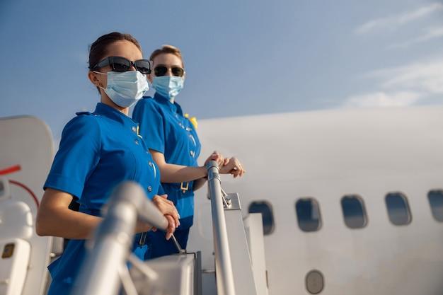 Twee jonge stewardessen in blauw uniform, zonnebrillen en beschermende gezichtsmaskers die naar de camera kijken, staande op de airstair op een dag. vliegtuigbemanning, bezetting, covid19-concept