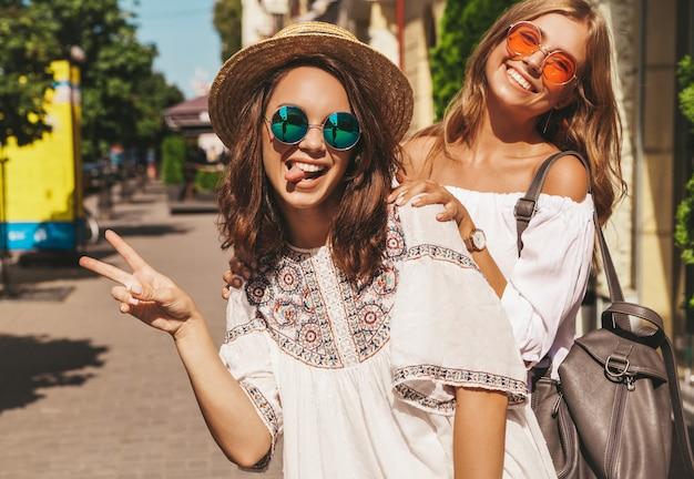 Twee jonge stijlvolle hippie brunette en blonde vrouwen modellen in zonnige zomerdag in witte hipster kleding poseren