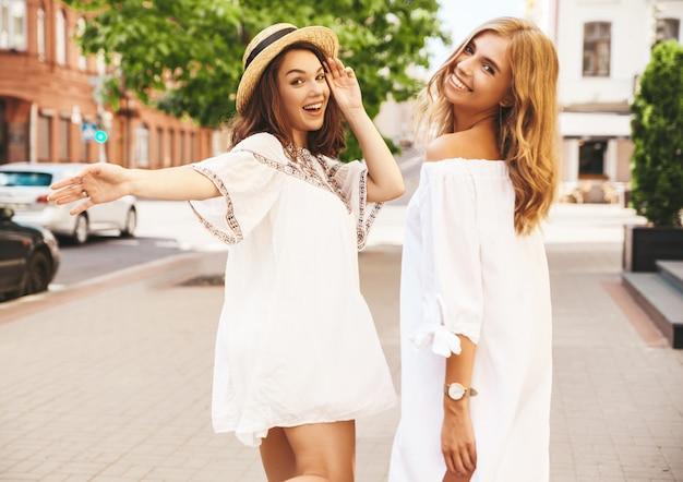 Twee jonge stijlvolle hippie brunette en blonde vrouwen modellen zonder make-up in zonnige zomerdag in witte hipster kleding poseren. draai je om en vraag om met ze mee te gaan