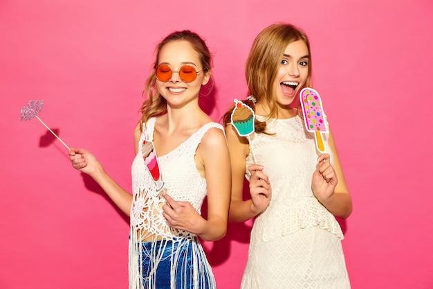 Twee jonge stijlvolle lachende blonde vrouwen eten rekwisieten zoet ijs en nep cocktail. positieve modellen in zomer hipster kleding poseren in de buurt van roze muur in zonnebril