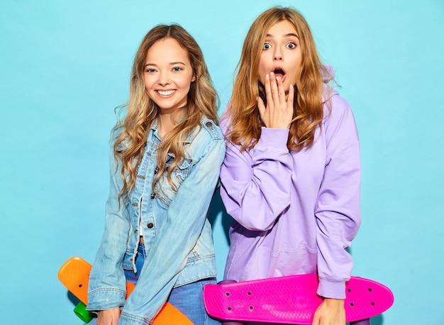 Twee jonge stijlvolle lachende blonde vrouwen met penny skateboards. modellen in zomer hipster sport kleding poseren in de buurt van blauwe muur. positieve vrouw