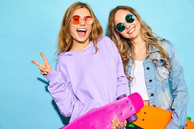 Twee jonge stijlvolle lachende blonde vrouwen met penny skateboards. modellen in zomer hipster sport kleding poseren in de buurt van blauwe muur. positieve vrouwen worden gek