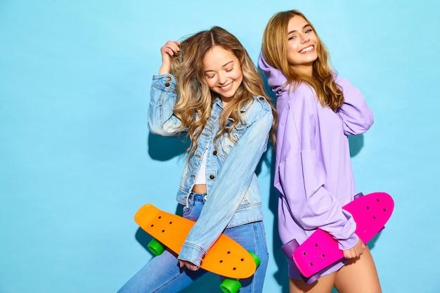 Twee jonge stijlvolle lachende blonde vrouwen met penny skateboards. vrouwen in de zomer hipster sport kleding poseren in de buurt van blauwe muur. positieve modellen