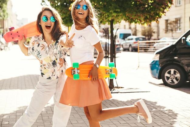 Twee jonge stijlvolle lachende hippie brunette en blonde vrouwen modellen in zomer hipster kleding met cent skateboard poseren. verras gezicht, emoties