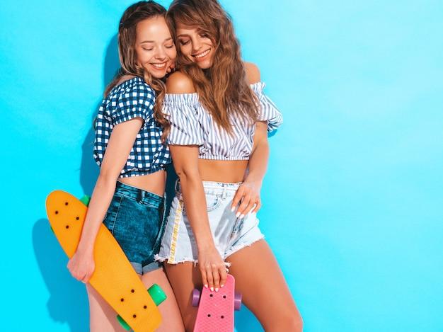 Twee jonge stijlvolle lachende mooie meisjes met kleurrijke penny skateboards. vrouw in de zomer geruit hemd kleren poseren. positieve modellen hebben plezier
