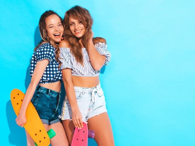 Twee jonge stijlvolle lachende mooie meisjes met kleurrijke penny skateboards. vrouwen in zomer geruite shirt kleding poseren. positieve modellen hebben plezier