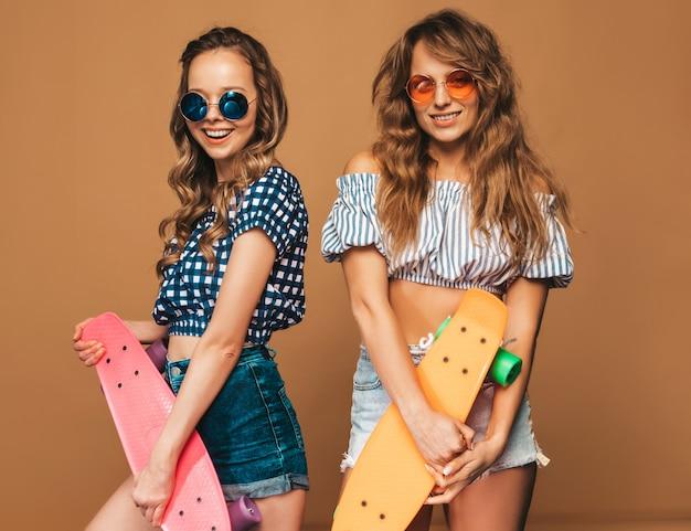 Twee jonge stijlvolle lachende mooie meisjes met penny skateboards. vrouwen in zomer geruite shirt kleding poseren in zonnebril. positieve modellen hebben plezier