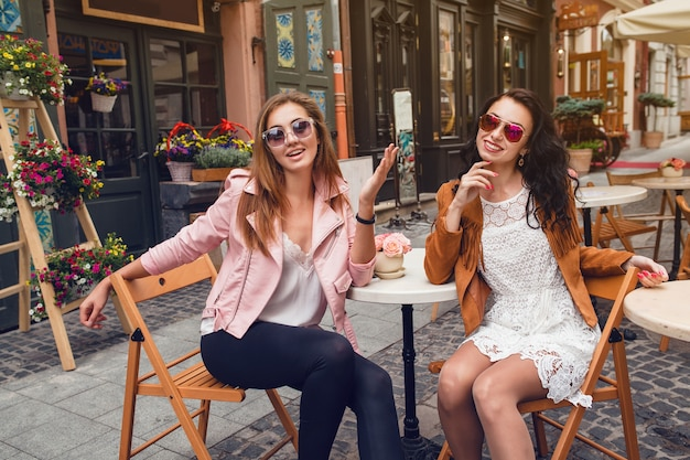 Twee jonge stijlvolle vrouwen zitten in café
