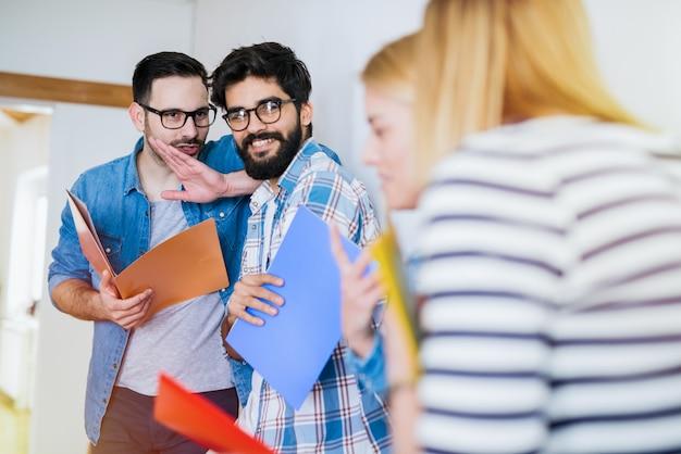 Twee jonge studentenjongens staan in een gang en praten over hun nieuwe schattige collega's. kijkend naar hen en lachend. Premium Foto