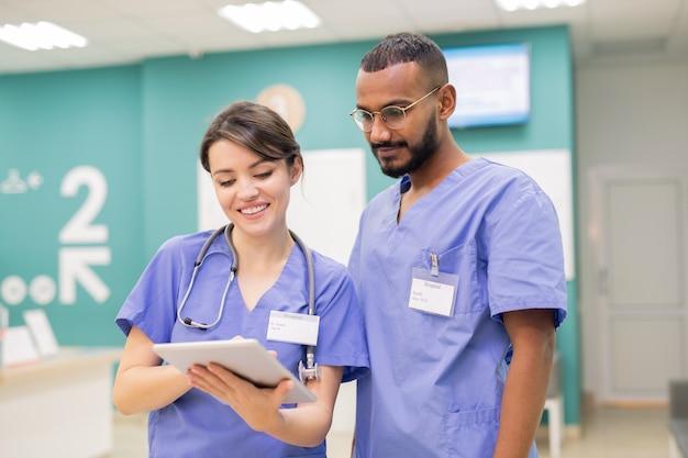 Twee jonge succesvolle clinici in uniform kijken door online medisch nieuws tijdens het scrollen in tablet op het werk