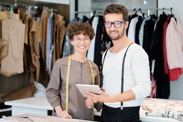 Twee jonge succesvolle creatieve ontwerpers staan in de werkplaats en werken aan nieuwe collectie