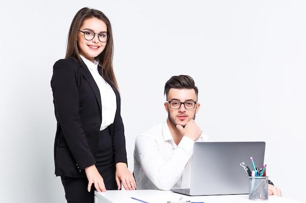 Twee jonge succesvolle mensen met laptop op witte muur