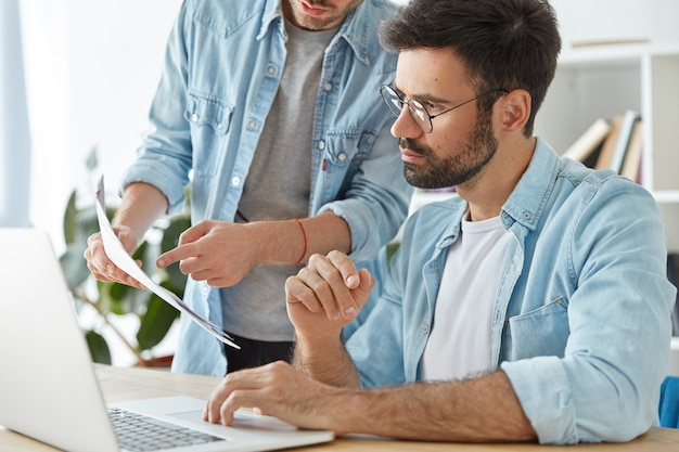 Twee jonge succesvolle ondernemers werken samen in coworking space