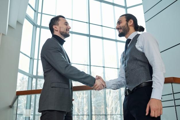 Twee jonge succesvolle zakenpartners of collega's in formalwear die elkaar begroeten door handdruk in bureaucentrum