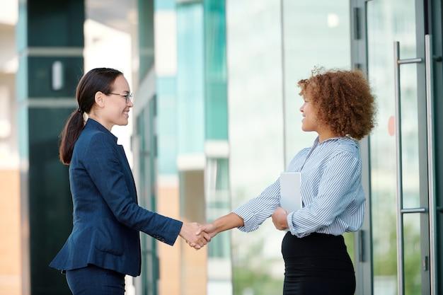 Twee jonge succesvolle zakenpartners of vrouwelijke collega's die elkaar verwelkomen door handdruk buitenshuis