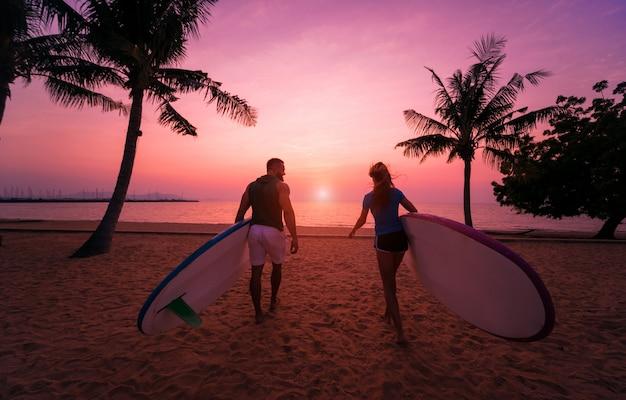 Twee jonge surfers gaan in de zee met surfplanken