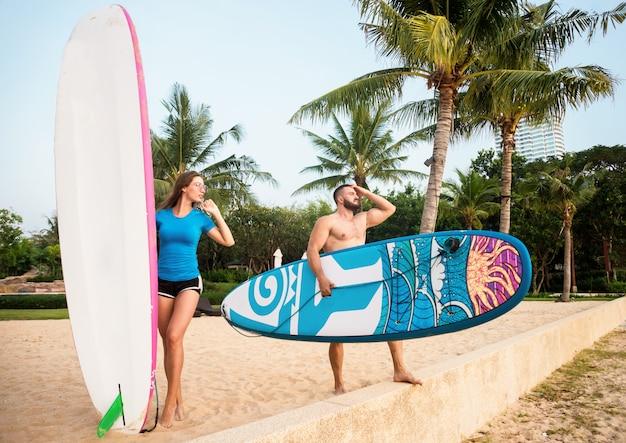 Twee jonge surfers met planken op het strand