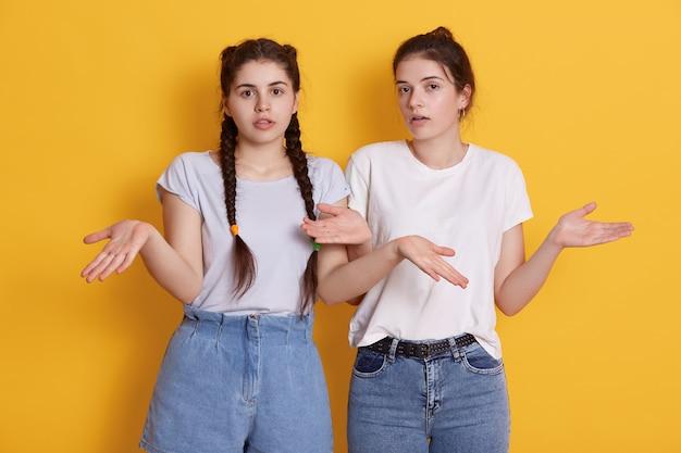 Twee jonge tiener jonge vrouwen in witte t-shirts poseren met de verspreiding van de handen